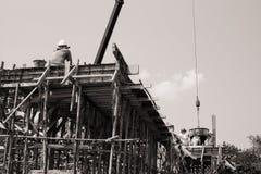 Μονοχρωματικός των εργαζομένων που φέρνουν το εμπορευματοκιβώτιο τσιμέντου που χύνει στο s στοκ φωτογραφία με δικαίωμα ελεύθερης χρήσης
