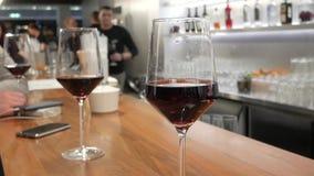 Μοντέρνα γυαλιά κρασιού σε έναν φραγμό απόθεμα βίντεο