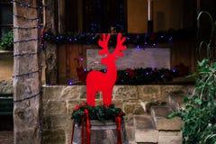 Μοντέρνα κόκκινα ελάφια Χριστουγέννων στα φω'τα βαρελιών και γιρλαντών, celebr Στοκ Φωτογραφία