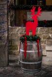 Μοντέρνα κόκκινα ελάφια Χριστουγέννων στα φω'τα βαρελιών και γιρλαντών, celebr Στοκ Εικόνες
