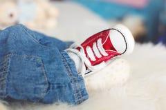 Μοντέρνα κόκκινα πάνινα παπούτσια στα μικρά νεογέννητα πόδια αγοράκι Στοκ φωτογραφία με δικαίωμα ελεύθερης χρήσης
