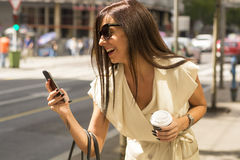 Μοντέρνα νέα γέλια brunette στο τηλέφωνο Στοκ Εικόνες