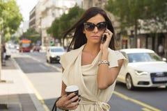 Μοντέρνα νέα γέλια brunette στο τηλέφωνο Στοκ Φωτογραφίες