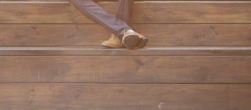 Μοντέρνα πόδια ατόμων ` s στα παπούτσια στο ξύλινο υπόβαθρο Στοκ εικόνα με δικαίωμα ελεύθερης χρήσης