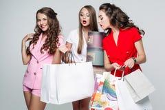 Μοντέρνες φίλες μετά από αγορές έκπληκτο να φανεί εσωτερικές τσάντες στοκ φωτογραφία με δικαίωμα ελεύθερης χρήσης
