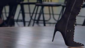 Μοντέρνες ψηλοτάκουνες μπότες γυναικών στα πόδια του προτύπου κατά τη διάρκεια defile στενών διαδρόμων στη επίδειξη μόδας απόθεμα βίντεο