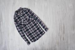 μοντέρνη έννοια Ελεγμένο πουκάμισο σε ένα ξύλινο υπόβαθρο FEM στοκ εικόνες