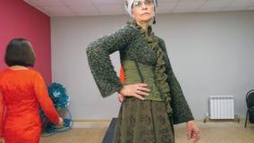 Μοντέρνη ανώτερη γυναίκα που περπατά στο στενό διάδρομο defile μόδας Ώριμο κομψό πρότυπο που παρουσιάζει νέα συλλογή φορεμάτων στ απόθεμα βίντεο