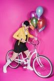 Μοντέρνη ανώτερη γυναίκα που φορά το κίτρινο σακάκι δέρματος που κρατά τα ζωηρόχρωμα μπαλόνια και που οδηγά το ποδήλατο Στοκ Εικόνα