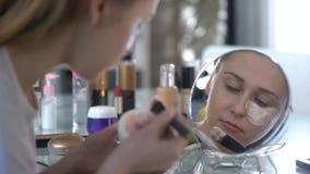 Μοντέρνη γυναίκα ήπια και προσεκτικά που βάζει την ενυδατική μάσκα κάτω από τα μάτια απόθεμα βίντεο