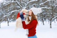 Μοντέρνη γυναίκα που κρατά ένα σκυλί και τα φιλιά αυτός Στοκ φωτογραφία με δικαίωμα ελεύθερης χρήσης
