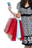 Μοντέρνη γυναίκα που περπατά με τις τσάντες αγορών και την πιστωτική κάρτα Στοκ Φωτογραφίες