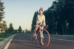 Μοντέρνη γυναίκα στο ποδήλατο το βράδυ Στοκ Εικόνες