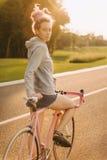 Μοντέρνη γυναίκα στο προσαρμοσμένο ποδήλατο στον ηλιόλουστο δρόμο πόλεων Στοκ Εικόνες