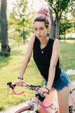 Μοντέρνη γυναίκα στο προσαρμοσμένο ποδήλατο στον ηλιόλουστο δρόμο πόλεων Στοκ φωτογραφία με δικαίωμα ελεύθερης χρήσης