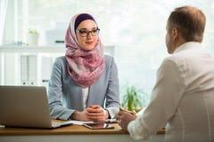 Μοντέρνη γυναίκα στο hijab που κάνει τη συνομιλία στο γραφείο με τον άνδρα στοκ φωτογραφίες με δικαίωμα ελεύθερης χρήσης