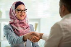 Μοντέρνη γυναίκα στο hijab που κάνει τη συνομιλία στο γραφείο με τον άνδρα στοκ εικόνες