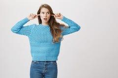 Μοντέρνη ελκυστική καυκάσια γυναίκα που καλύπτει τα αυτιά με τους αντίχειρες και που κοιτάζει δεξιά με κατάπληκτος και ανικανοποί Στοκ Εικόνα