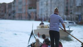 Μοντέρνη ενετική ωθώντας γόνδολα λεμβούχων με τους ξένους τουρίστες, χρήματα απόκτησης απόθεμα βίντεο
