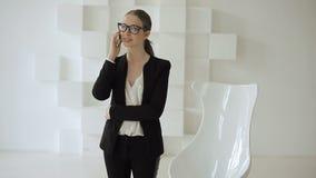 Μοντέρνη επιχειρηματίας στην επίσημη ένδυση με την κλήση smartphone απόθεμα βίντεο