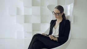 Μοντέρνη επιχειρηματίας στην επίσημη ένδυση με τη συνεδρίαση ταμπλετών στην άσπρη καρέκλα απόθεμα βίντεο