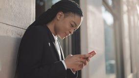 Μοντέρνη επιχειρηματίας afro που χρησιμοποιεί το smartphone που στέκεται στην οδό κοντά στο επιχειρησιακό κέντρο Μαύρος μοντέρνος απόθεμα βίντεο