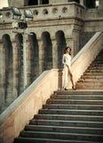 μοντέρνη θέτοντας γυναίκα Νέα γυναίκα στο άσπρο μακρύ φόρεμα που επιταχύνει τη σκάλα Στοκ Εικόνες