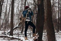 Μοντέρνη κάμερα ταξιδιωτικής εκμετάλλευσης hipster και παραγωγή της φωτογραφίας στο χιόνι στοκ εικόνες