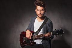 Μοντέρνη κιθάρα παιχνιδιού καλλιτεχνών στο σκοτεινό υπόβαθρο στούντιο Στοκ Εικόνες