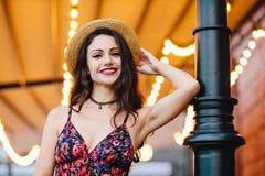 Μοντέρνη κομψή γυναίκα που φορά το φόρεμα με την τυπωμένη ύλη λουλουδιών και το καπέλο αχύρου, που θέτουν στη κάμερα με το χαμόγε στοκ εικόνα με δικαίωμα ελεύθερης χρήσης