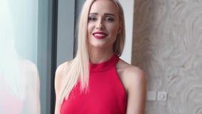 Μοντέρνη κομψή ξανθή γυναίκα στο εγχώριο καθιστικό, που φορά το κόκκινο προκλητικό φόρεμα φιλμ μικρού μήκους