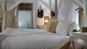 Μοντέρνη κρεβατοκάμαρα στο ξενοδοχείο SPA, τα ελαφριά έπιπλα χρώματος και τον άσπρο μεγάλο θόλο κρεβατιών απόθεμα βίντεο