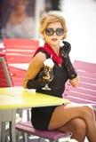 Μοντέρνη κυρία με λίγο μαύρο φόρεμα και κόκκινη συνεδρίαση μαντίλι στην καρέκλα στο εστιατόριο, υπαίθριος πυροβολισμός στην ηλιόλ στοκ φωτογραφία