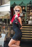 Μοντέρνη κυρία με το κοντό μαύρο φόρεμα δαντελλών και τα κόκκινα υψηλών τακούνια μαντίλι και, υπαίθριος πυροβολισμός Νέος ελκυστι στοκ εικόνες