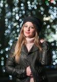 Μοντέρνη κυρία που φορά την ΚΑΠ και το μαύρο σακάκι υπαίθριες στο τοπίο Χριστουγέννων με τα μπλε φω'τα στο υπόβαθρο. Πορτρέτο του  Στοκ Εικόνα