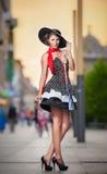 Μοντέρνη κυρία που φορά την τοποθέτηση μαύρων καπέλων στην οδό Στοκ εικόνα με δικαίωμα ελεύθερης χρήσης