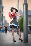 Μοντέρνη κυρία που φορά την τοποθέτηση μαύρων καπέλων στην οδό Στοκ φωτογραφία με δικαίωμα ελεύθερης χρήσης