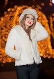 Μοντέρνη κυρία που φορούν την άσπρη γούνα ΚΑΠ και παλτό υπαίθριο με τα φωτεινά φω'τα Χριστουγέννων στο υπόβαθρο. Πορτρέτο της νέας Στοκ Εικόνες