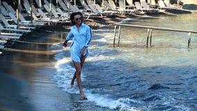 Μοντέρνη κυρία στη δύσκολη παραλία θάλασσας φιλμ μικρού μήκους