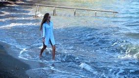 Μοντέρνη κυρία στη δύσκολη παραλία θάλασσας απόθεμα βίντεο