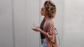 Μοντέρνη μαύρη γυναίκα με το smartphone στην οδό απόθεμα βίντεο