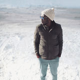 Μοντέρνη νέα αφρικανική φθορά ατόμων μόδας γυαλιά ηλίου, πλεκτά καπέλο και σακάκι στη χειμερινή ημέρα πέρα από το χιόνι Στοκ Εικόνες