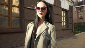 Μοντέρνη νέα γυναίκα στα γυαλιά ηλίου και παλτό ενάντια στο καφετί κτήριο στην οδό απόθεμα βίντεο