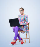 Μοντέρνη νέα γυναίκα στα γυαλιά που κάθεται σε μια καρέκλα με ένα lap-top Στοκ φωτογραφία με δικαίωμα ελεύθερης χρήσης