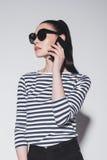 Μοντέρνη νέα γυναίκα στην ομιλία γυαλιών ηλίου στο smartphone που απομονώνεται στο γκρι Στοκ Εικόνες