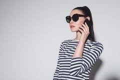 Μοντέρνη νέα γυναίκα στην ομιλία γυαλιών ηλίου στο smartphone που απομονώνεται στο γκρι Στοκ εικόνα με δικαίωμα ελεύθερης χρήσης