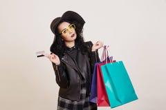 Μοντέρνη νέα γυναίκα στο μαύρο καπέλο με την πιστωτική κάρτα και colore στοκ φωτογραφία με δικαίωμα ελεύθερης χρήσης