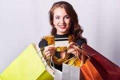 Μοντέρνη νέα γυναίκα brunette που κρατά τις ζωηρόχρωμες τσάντες αγορών και την πιστωτική κάρτα στοκ φωτογραφίες