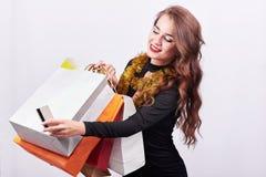 Μοντέρνη νέα γυναίκα brunette που κρατά τις ζωηρόχρωμες τσάντες αγορών και την πιστωτική κάρτα στοκ εικόνα με δικαίωμα ελεύθερης χρήσης