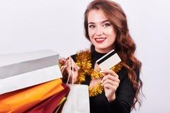 Μοντέρνη νέα γυναίκα brunette που κρατά τις ζωηρόχρωμες τσάντες αγορών και την πιστωτική κάρτα στοκ φωτογραφία με δικαίωμα ελεύθερης χρήσης